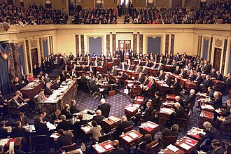 Impeachment of Bill Clinton - Floor proceedings of the U.S. Senate during the trial of President Bill Clinton in 1999, Chief Justice William Rehnquist presiding. House managers are seated beside the quarter-circular tables on the left and the president's personal counsel on the right.