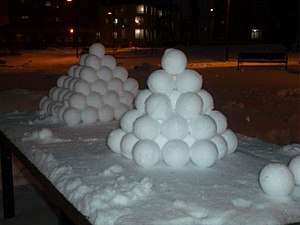 Close-packing of equal spheres -  Snowballs stacked in preparation for a snowball fight. The front pyramid is hexagonal close-packed and rear is face-centered cubic.