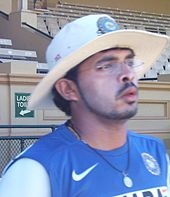 Young man wearing glasses and a white broad brimmed hat. He is wearing a black string necklace, blue t-shirt, and has a thin sideburn that links to a narrow beard, and a small thin moustache. He is wearing a light layer of white zinc cream on his face. A brick stand for spectators is in the background.