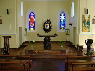 Pollagh - St Mary's Church The Bog oak (or Elm) altar in the Church, with stained glass windows of the Harry Clarke Studios in background