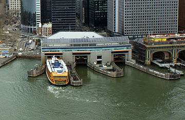 Three docks can be seen from the air, and next to them is a covered ferry terminal. This is an aerial view over a river.