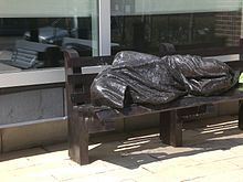 A photograph of a bronze statue of a person covered in a blanket and lying on a park bench all in front of a building with glass windows on a sunny day