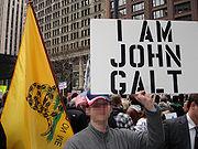 街頭デモで「I am John Galt」と大文字で書かれたプラカードを掲げる男性