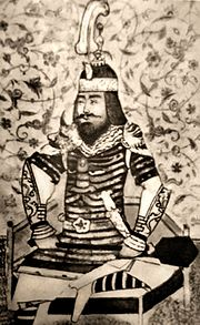 Black-and-white copy of a Persianate miniature, showing a bearded middle-aged man, wearing armour and helmet, seated cross-legged on a low throne