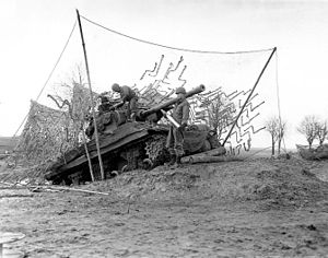 2nd Armored Division (United States) - Btryv C, 702 TD Bn., 2nd Armored Division, tank destroyer on dug-in ramp has plenty of elevation to hurl shells at long range enemy targets across the Roer River. L-r: Sgt. Earl F. Schelz, Pvt. George E. Van Horne, and Pfc. Samuel R. Marcum. 16 December 1944.