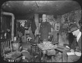 Two officials of the New York City Tenement House Department inspect a cluttered basement living room, ca. 1900 - NARA - 535469.tif
