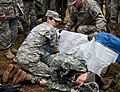 U.S. Army Sgt. Dayna Taylor, a licensed practical nurse with Alpha Company, Madigan Army Medical Center, demonstrates putting a causality on a medical litter during Expert Field Medical Badge training at Joint 130404-A-FS521-157.jpg