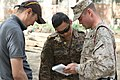 U.S. Marine Corps Sgt. Ben Eberle, right, a combat correspondent with Marine Corps Forces Pacific, reviews interview questions with Mongolian Armed Forces 1st Lt. Tumurbaatar Tulga, center, with 017 Construction 130725-M-DR618-053.jpg