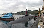 Submarine being assisted into a mooring position at a pier by a tug.