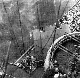 """Nevada-class battleship - A view looking down a 5""""/38 cal gun and quad 40mm Bofors mount of USS Nevada during the Normandy landings, 6 June 1944. The main deck is covered with spent shell casings as she serves as a support gunfire ship"""