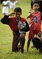 US Navy 050106-N-4166B-488 A lone hand salute is rendered by an Indonesian child as a U.S. Navy helicopter lifts off after delivering food and water in Lamno, Sumatra, Indonesia.jpg