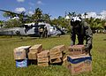 US Navy 050107-N-5376G-007 Aviation Warfare System Operator 2nd Class Cory Merritt of Troy, Mich., unload food and water in the town of Meulaboh, Sumatra, Indonesia.jpg