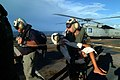 US Navy 050407-N-6504N-010 Retired Rear Adm. William McDaniel, left, leads Chief Hospital Corpsman Patrick Nardulli as he carries an Indonesian child from an MH-60S Seahawk helicopter to be medically treated.jpg