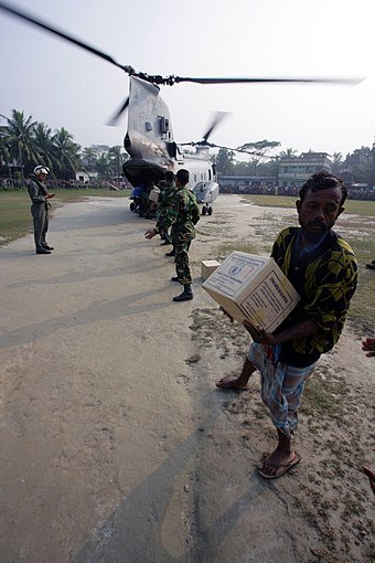 Bangladeshi citizens offload food rations from a US Marine CH-46E helicopter of 11th Marine Expeditionary Unit after Tropical Cyclone Sidr in 2007