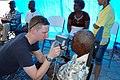 US Navy 090417-F-7885G-005 Hospital Corpsman 3rd Class Paul Mason, an optician embarked aboard the Military Sealift Command hospital ship USNS Comfort (T-AH 20) treats a Haitian man at the Cite Soleil medical site.jpg