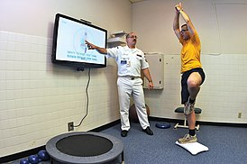 US Navy 090702-N-1783P-003 Hospital Corpsman 1st Class Guy Duke, left, and Electronics Technician 3rd Class Joshua Benedict demonstrate how the Physical therapy Department at Naval Health Clinic, Charleston use the Wii Fit's yoga.jpg