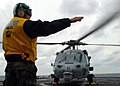 US Navy 100204-N-7058E-230 Aviation Electrician's Mate 3rd Class David Harden, assigned to Helicopter Sea Combat Squadron (HSC) 22, signals to begin a hot refueling of an MH-60S Sea Hawk helicopter.jpg