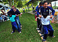 US Navy 100609-N-7643B-221 U.S. and Royal Malaysian Navy sailors and children from the Rumah Wawasan Children's Home participate in a team relay race.jpg