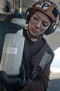 US Navy 120103-N-OY799-025 Aviation Ordnanceman Airman Samantha Phillips collects fuel samples from an F-A-18E Super Hornet from the Black Aces of.jpg
