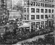 "On April 19, 1917 the cowcatcher of the Flatiron Building United Cigar Store was transformed into a mock fort for the ""Wake up America Day"" parade."