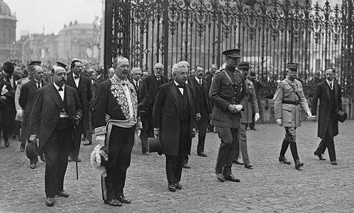 Zwart-witfoto van een groep mannen (burgers en soldaten) die een binnenplaats betreden, omringd door een poort