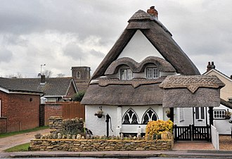 Wilstead - A thatched cottage in Wilstead, with the tower of All Saints Church visible in the background