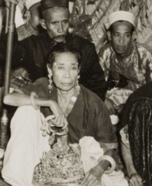 A black-and-white picture of a woman holding a crown, with two other people in the background