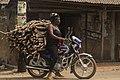 Woman transporting wood on her motorcycle (Okada).jpg