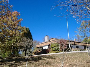The visitor center is depicted as a building on a hill, surrounded by trees with autumn foliage and a clear blue sky.