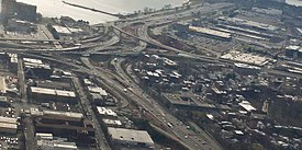 A series of highway ramps with multiple cars on them. A body of water is next to them and they are surrounded by buildings