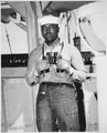 """Looking to sea from the signal bridge is Napoleon Reid, Seaman 2-c., USNR, shown standing on lookout watch on a ship so - NARA - 535846.tif"