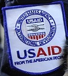 """""""UNITED STATES AGENCY (for) INTERNATIONAL DEVELOPMENT USAID FROM THE AMERICAN PEOPLE"""" patch detail, Flickr - DVIDSHUB - Operation Tomodachi (Image 1 of 52) (cropped).jpg"""