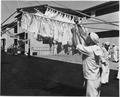 (Sailor hanging wash on laundry day or possibly learning to tie knots or hand signal flags at the Naval Training... - NARA - 295576.tif
