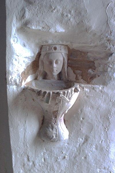 Pierre calcaire XVIe constitué par le réemploi de deux morceax de statue de femme: le buste et le haut de la jupe ont été placés tête en bas et le l'intérieur de la jupe a été creusé pour formé la vasque du bénitier. La tête représente Ste Catherine ou Ste Barbe