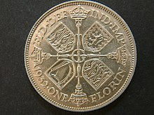 One side of a 1932-dated silver coin, with an arrangement of crowns and sceptres