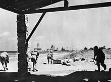 Soldiers advance under fire along a desert road towards a wireless station