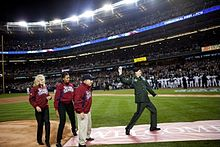 "A man in a green military uniform prepares to throw a ball, while two women and a man on the left wearing red jackets with ""World Series"" on the chest look on."