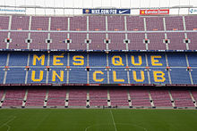 "The words ""Més que un club"" are painted in yellow on the blue seats of the stadium"