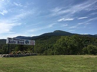 Mount Washington Auto Road - Sign at the bottom of the road, with Mount Washington visible ahead
