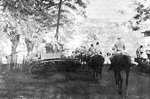 A long column of men on horseback moving down a road. A tank is parked beside the road.