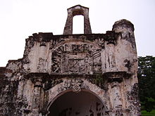 Stained ruin of a stone building, showing a central arch, flanked by two columns, with a stone relief above the arch, also flanked by two columns, and a second free-standing arch perched on the very top of the ruin.