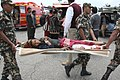 A rescued injured girl on a stretcher being taken for emergency medical treatment in quake hit Nepal.jpg