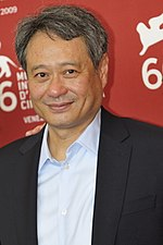An Asian male wearing a grey jacket over an unbuttoned blue shirt is standing in front of a red wall with white text.