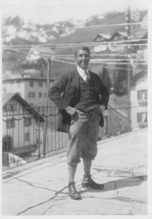 A black and white photo of a man standing on a street. He has his hands on his hips and is smiling towards the camera.