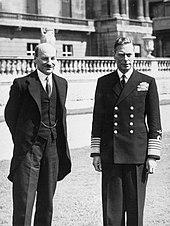 George VI en uniforme d'amiral et Attlee en costume se tiennent devant une balustrade extérieure