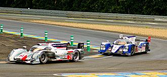 2013 24 Hours of Le Mans - The No. 2 Audi R18 e-tron quattro followed closely by the No. 8 Toyota TS030 Hybrid at Mulsanne corner