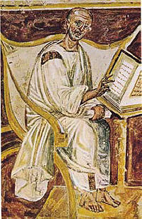 Painting detail of a bald man in white robes and bare feet, wearing glasses, seated in a white chair reading a book