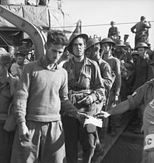 A line of unarmed soldiers disembarking from a ship down a gangway.
