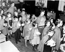A group of small children and their teachers in a line, wearing brown capes and carrying food in their hands