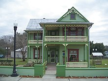 a two-story green house with Victorian ornamentation